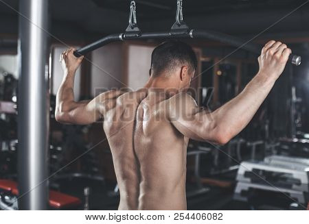 Ripped Man Is Exercising Latissimus With Outfit Indoors