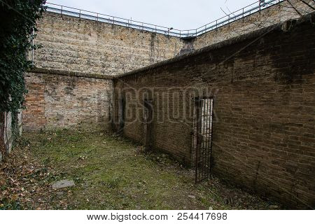 Unkempt Courtyard Of An Old Prison Full Of Weeds And Cells.
