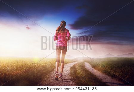 Slim fit woman jogging on a dirt track through grassland at sunrise with a bright glow on the horizon over distant mountains viewed from the rear in a health and fitness concept