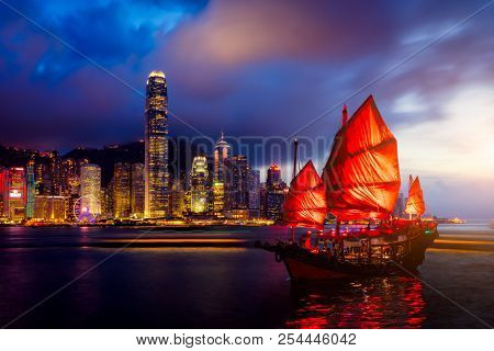 Hong Kong City Skyline With Tourist Sailboat At Night. View From Across Victoria Harbor Hong Kong.
