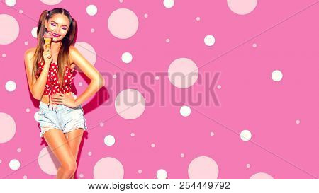 Beauty joyful sexy model girl smiling, dancing and posing with Ice cream cone close-up. Young woman holding Icecream scoop in waffle cone. White background. Strawberry, raspberry Sweet dessert poster