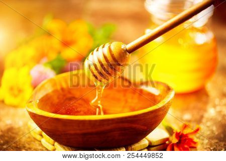Honey dripping from honey dipper in wooden bowl.  Close-up. Healthy organic Thick honey pouring from the wooden honey spoon, closeup. Sweet dessert background