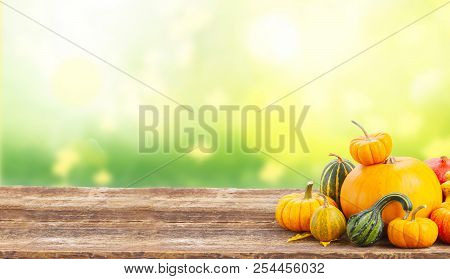 Pile Of Orange Pumpkins With Fall Leaves On Wooden Table Over Fall Background Banner