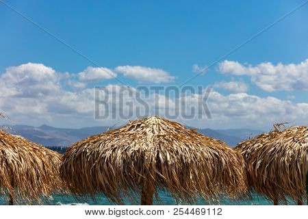 Straw umbrellas closeup, windy beach and blue sky with clouds background