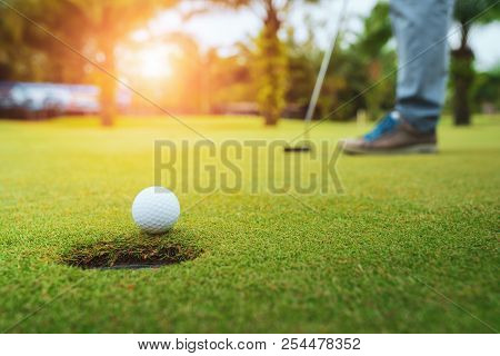 poster of Golfer putting golf ball on the green golf, lens flare on sun set evening time, Pro Golf long putting golf ball in to the hole, sunset scene time.