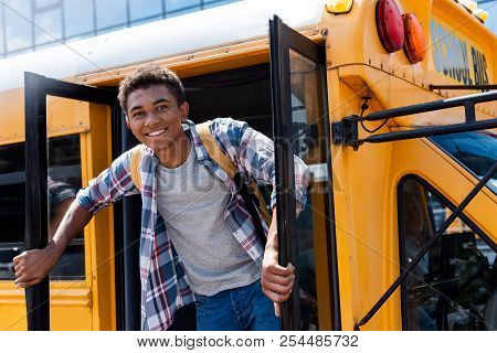 Happy Teen African American Schoolboy Standing In Door Of School Bus And Looking At Camera