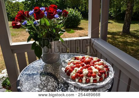 Summer Treat With A Strawberry Cake On A Table In A Garden