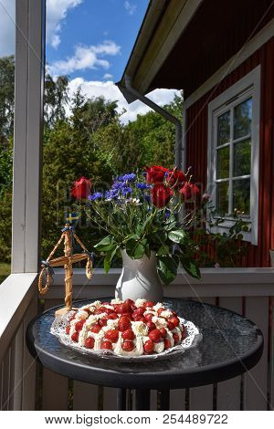 Summer Decorations With Strawberry Cake, Flowers And A Small May Pole On A Table On The Porch