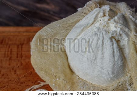 Cheese, cottage cheese on a wooden background, fresh cottage cheese in gauze, dairy product, healthy food. View from above. Goat, cow-baked cottage cheese in a rustic style. poster