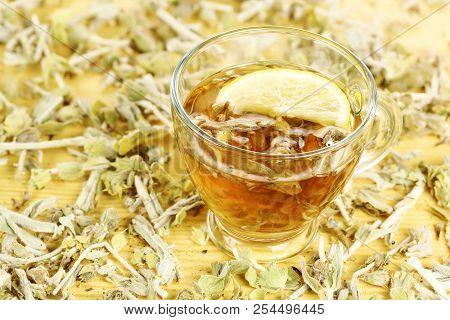 Cup Of Mountain Tea With Lemon Slice And Tea Leaves On Wood