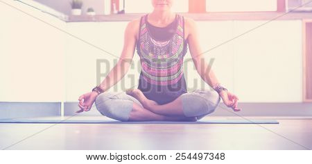 Young woman doing yoga at home in the lotus position. Yoga. Woman. Lifestyle