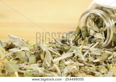 Jar Of Mountain Tea On Wooden Surface