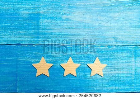 Three Stars On A Blue Background. The Concept Of Rating And Evaluation. The Rating Of The Hotel, Res
