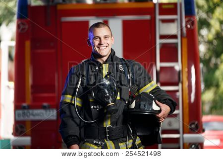 Photo of happy fireman with gas mask and helmet near fire engine