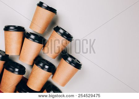 Many Brown Craft Cups Of Coffee To Go On Red And Grey Background. Flat Lay Stye.