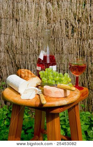Cheese board outdoor with cheese bread and wine
