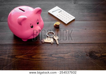 Money for buy car. Moneybox in shape of pig near keychain in shape of car, coins, calculator on dark wooden background copy space poster