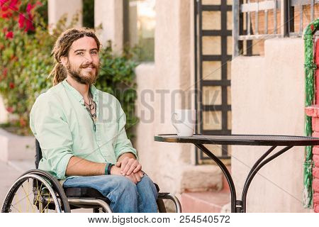 Smiling Young Man In Wheelchair At Outdoor Table