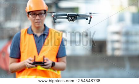 Young Asian Engineer Man Flying Drone Over Construction Site. Using Unmanned Aerial Vehicle (uav) Fo