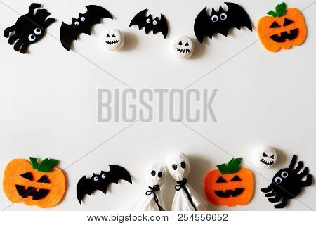 Top View Of Halloween Crafts, Orange Pumpkin, Ghost And Spide On White Background With Copy Space Fo