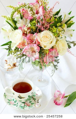 beautiful flowers in vase , cup of tea and biscuits