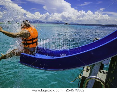 Asian Man Playing The Slider On The Boat With Amzing Idyllic Ocean And Blue In Vacation Time.summer