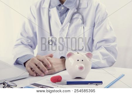 Doctor And Piggy Bank On Table Medical Fee For Health Care. Finance And Insurance Concept.