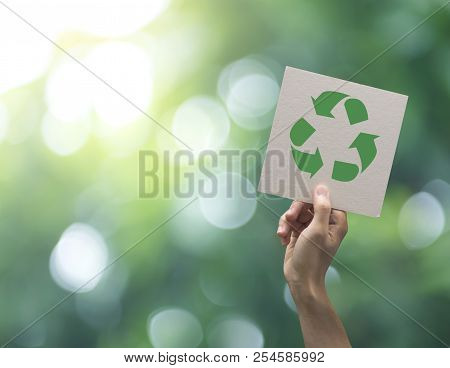 Hand Holding Recycle Symbol On Green Bokeh Background. Eco And Save The Earth Concept.