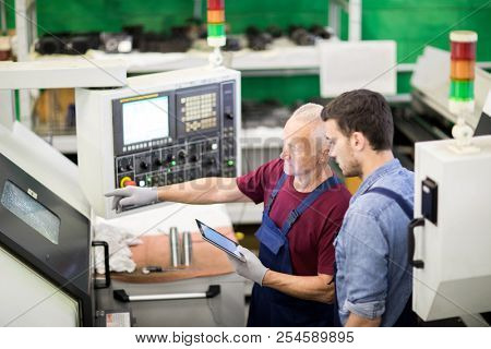 Mature foreman controlling the process of machine on his tablet pc and showing how its work to the worker