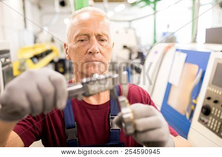 Concentrated skilled mature worker working with worktools at industrial factory