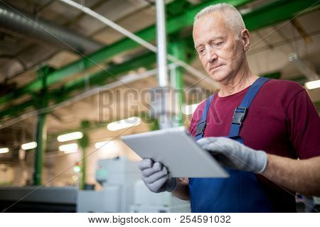 Mature professional worker using digital tablet at manufacturing plant