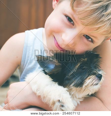 Caucasian Boy Embraces Puppy Yorkshire Terrier