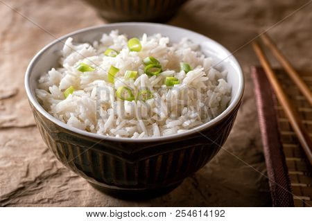 A Bowl Of Delicious Plain Steamed Rice With Scallion Garnish.