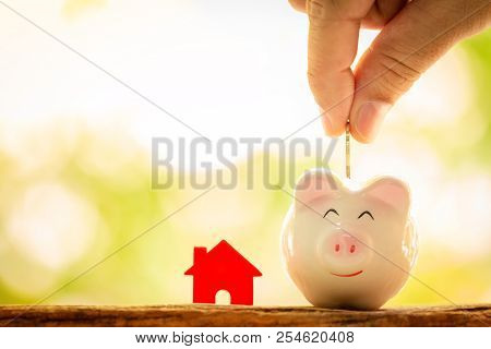 Investor Hand Hold A Coin With Save In The Piggy Bank And A Red Home Model For Family Put On The Woo