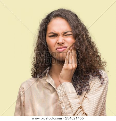 Young hispanic business woman touching mouth with hand with painful expression because of toothache or dental illness on teeth. Dentist concept.
