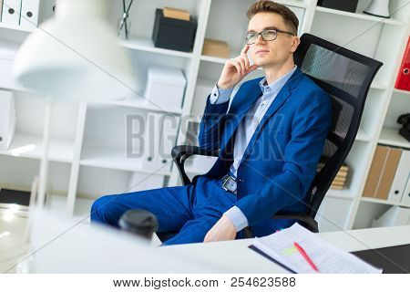 A Young Man Is Sitting At A Table In The Office.