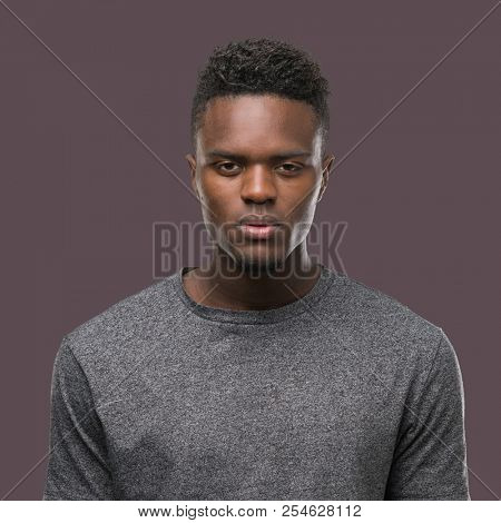 Young african american man wearing grey t-shirt with serious expression on face. Simple and natural looking at the camera.