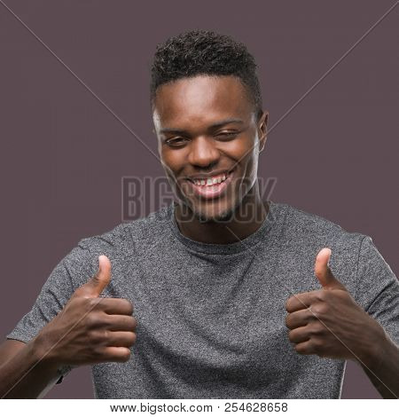 Young african american man wearing grey t-shirt success sign doing positive gesture with hand, thumbs up smiling and happy. Looking at the camera with cheerful expression, winner gesture.