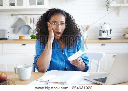 Worried Emotional Young Afro American Woman In Glasses Opening Mouth Widely, Being Shocked With Amou