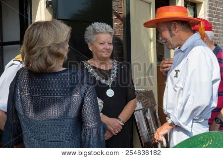 Alkmaar, Netherlands - July 20, 2018: Cheese Father, head of the cheese carriers Guild is talking to deputy mayor of Alkmaar, mrs. Elly Konijn-Vermaas