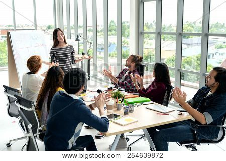 Young Asian Businesswoman Explain Idea To Group Of Creative Diverse Team At Modern Office. Manager S