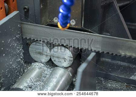 The  Band Saw Machine Cutting Raw Metals Rods The  With The Coolant Fluid.the Industrial Sawing Mach