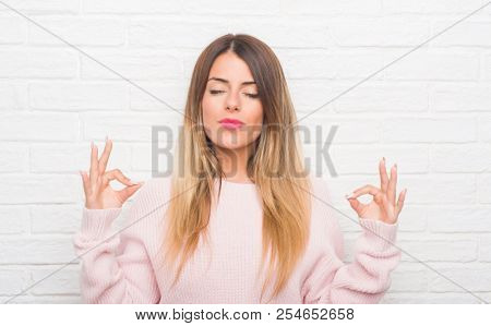 Young adult woman over white brick wall wearing winter outfit at home relax and smiling with eyes closed doing meditation gesture with fingers. Yoga concept.