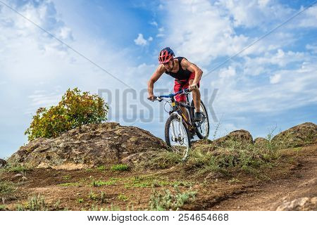 Cyclist Descending Down The Rock On A Mountain Bike, An Active Lifestyle.