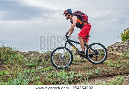 Cyclist Riding A Mountain Bike On Rocks On The Blue Sky Background.