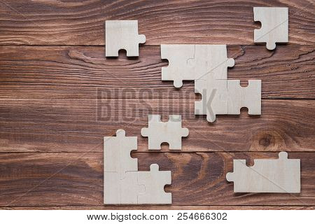 Incomplete wooden puzzles on brown wooden desk, top view, flat lay. Frame with puzzle. The concept of logical thinking, business, conundrum. Business concept with jigsaw puzzle on wooden background. poster
