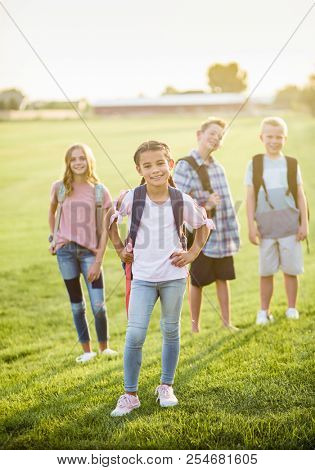 Portrait photo of a diverse group of smiling elementary school students standing in a school yard wearing backpacks. Back to school photo