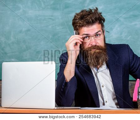 Examiner Full Of Doubts Sit At Table Chalkboard Background. Tricky Examinator Hesitates About Mark.
