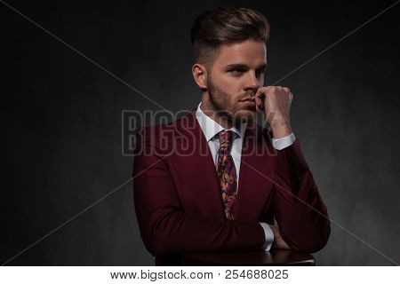portrait of pensive elegant man resting his hands on wooden chair and looking to side while standing on grey wallpaper background