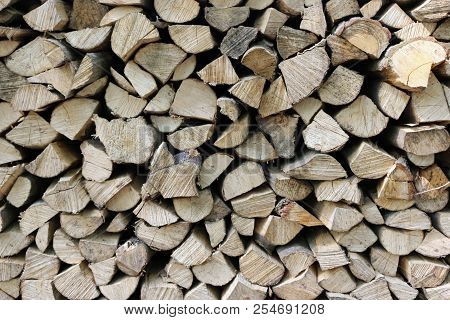 Split And Round Logs From A Coppice Woodland Drying In A Stack For Firewood Making An Attractive Col